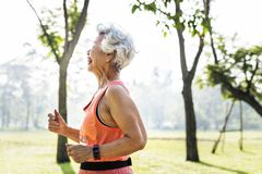 Senior athlete running in the park. Alone happily royalty free stock images