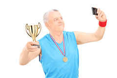 Senior athlete taking selfie with trophy in hand Royalty Free Stock Images