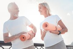 Senior athletic couple standing and communicating. Common training. Senior athletic gray-haired couple standing on the street holding gum rugs and communicating Stock Photography