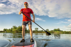 Senior athletic paddler on paddleboard Stock Images