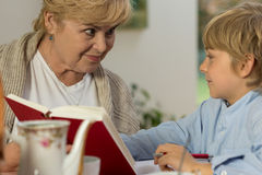 Senior babysitter caring about schoolboy. Portrait of senior babysitter caring about schoolboy Royalty Free Stock Photo