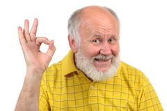 Senior bald man's gestures. Senior funny bald man in yellow t-shirt is shows gestures and grimaces Royalty Free Stock Photos