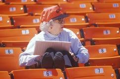 Senior Baseball fan taking statistics during game, Candlestick Park, San Francisco, CA Stock Photo