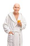 Senior in a bathrobe holding an orange juice Royalty Free Stock Photo