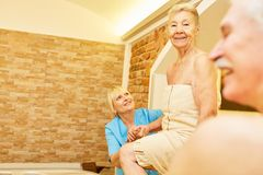 Senior bathes with care in the Jacuzzi. Senior baths with care in the whirlpool of the spa in an aquatic therapy stock photography