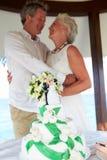 Senior Beach Wedding Ceremony With Cake In Foreground Stock Image