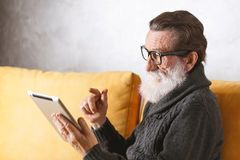 Senior Man Reading Book On The Digital Tablet royalty free stock images