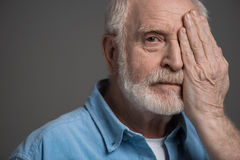 Senior bearded man reviewing eyesight isolated on grey in studio Royalty Free Stock Images