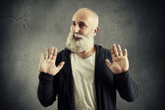 Senior bearded man showing refusal sign. And looking at camera over dark background Stock Images