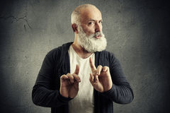 Senior bearded man showing refusal sign. And looking at camera over dark wall Royalty Free Stock Images