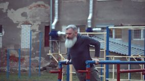 Senior bearded man with strong muscular arms exercising outdoors, doing pull ups, elderly male performing pulling exercise on hori