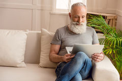 Senior bearded man using laptop while sitting on sofa at home Stock Photo