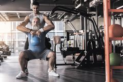 Concentrated old male having workout in gym with young instructor. Senior bearded men is doing kettlebell goblet squats with his professional trainer who is stock photography