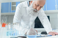 Senior bearded scientist in white coat writing in clipboard on tanle with flasks in chemical laboratory Stock Photography