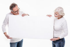 Senior beautiful couple with empty white board. Stock Photos