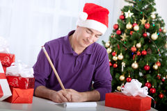Senior beautiful man writes wishes to santa claus Royalty Free Stock Photo