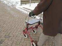 Senior behind wheeled walker in snow royalty free stock photos