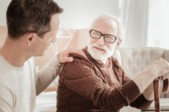 Senior bespectacled man looking at son and smiling. My son. Senior bespectacled pleasant men sitting in the bright room looking at son and smiling Stock Photo