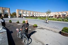 Senior with bicycle walk through Imam Square with historical buildings Royalty Free Stock Photos