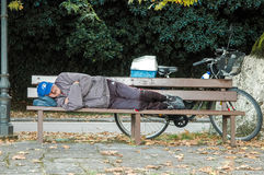 Senior bicyclist rests on a bench Stock Image