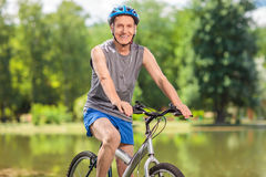 Senior biker with a blue helmet posing on his bicycle Stock Photography