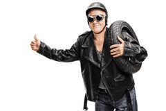 Senior biker carrying a tire and hitchhiking Royalty Free Stock Images