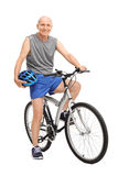 Senior biker holding a blue helmet seated on his bike Royalty Free Stock Image