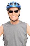 Senior biker posing with a blue helmet Stock Images