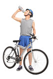 Senior biker standing behind a bike and drinking water. Full length portrait of a senior biker standing behind his bicycle and drinking water isolated on white Stock Images