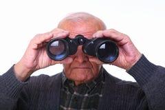 Senior with binoculars. Portrait of caucasian senior looking with binoculars Stock Photo