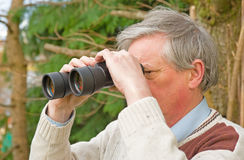 Senior with binoculars. Royalty Free Stock Image