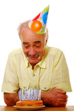 Senior birthday. Senior man looking down at his birthday cake with lots of candles Royalty Free Stock Images