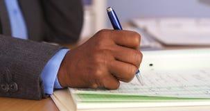 Senior black businesswoman taking notes on pad. Closeup of senior black businesswoman taking notes on pad Stock Photos