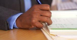 Senior black businesswoman taking notes on pad. Closeup of senior black businesswoman taking notes on pad Royalty Free Stock Image