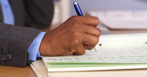 Senior black businesswoman taking notes on pad. Closeup of senior black businesswoman taking notes on pad Royalty Free Stock Photography