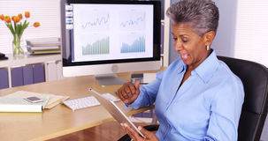 Senior black businesswoman talking on smartphone and using tablet Stock Image