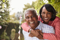 Senior black couple piggyback in garden looking at camera Royalty Free Stock Photos