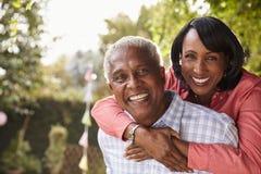 Senior black couple piggyback in garden looking at camera royalty free stock photos