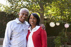 Senior black couple in their garden looking to camera stock images
