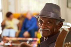 Senior Black Man With Hat Looking At Camera In Hospice. Portrait of elderly black men looking at camera in retirement home, with group of friends in background Royalty Free Stock Images