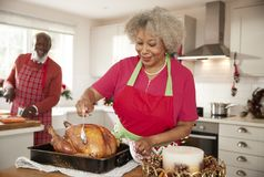 Senior black woman basting a roast turkey in preparation for Christmas dinner, her husband chopping vegetables in the background, royalty free stock photo