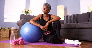 Senior Black woman sitting on floor with exercise equipment. Black woman sitting on floor with exercise equipment Royalty Free Stock Photos