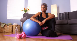 Senior Black woman sitting on floor with exercise equipment Royalty Free Stock Photography