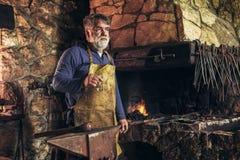 Senior blacksmith forge iron. At work royalty free stock photography