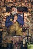 Senior blacksmith forge iron. At work stock image
