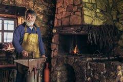Senior blacksmith forge iron. At work royalty free stock photo