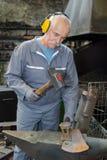 Senior blacksmith forging molten metal on anvil royalty free stock image