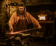Senior blacksmith forging the molten metal on the anvil in smithy Royalty Free Stock Image
