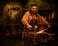 Senior blacksmith forging the molten metal on the anvil in smithy Royalty Free Stock Images