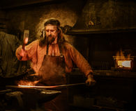 Senior blacksmith forging the molten metal on the anvil in smithy Royalty Free Stock Photo